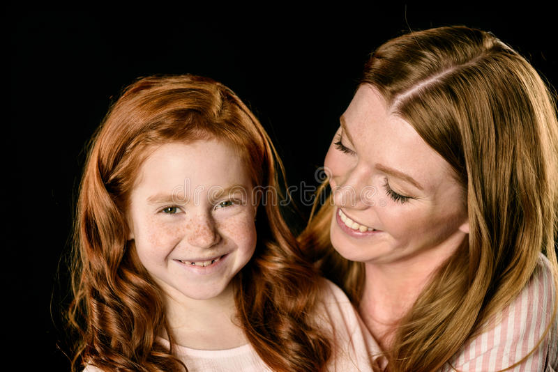 Portrait of smiling mother looking at adorable redhead daughter stock photo
