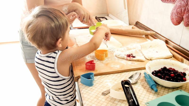 Portrait of young smiling mother teaching her 3 years old toddler boy baking and making cookies on kitchen. Portrait of smiling mother teaching her 3 years old royalty free stock images