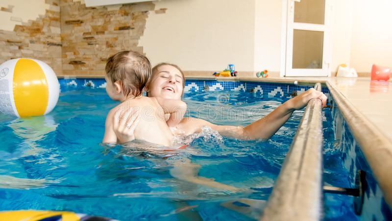 Portrait of happy smiling mother with 3 years old little son swimming in the pool at gym. Family raelaxing, having fun royalty free stock photos
