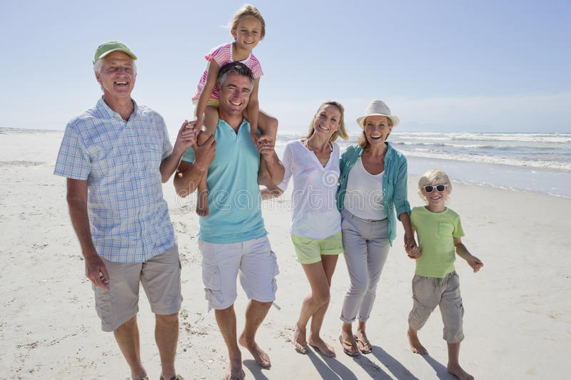 Portrait of smiling multi-generation family walking on sunny beach royalty free stock photography