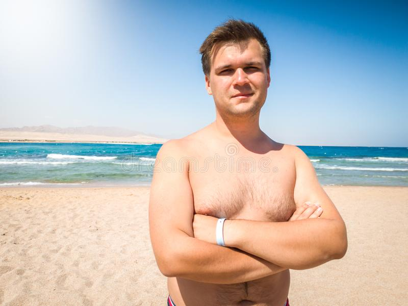 Portrait of smiling muscular young man posing on the beach against sea and blue sky royalty free stock images