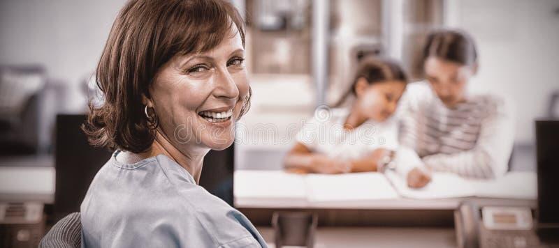 Portrait of smiling nurse sitting at desk stock photos