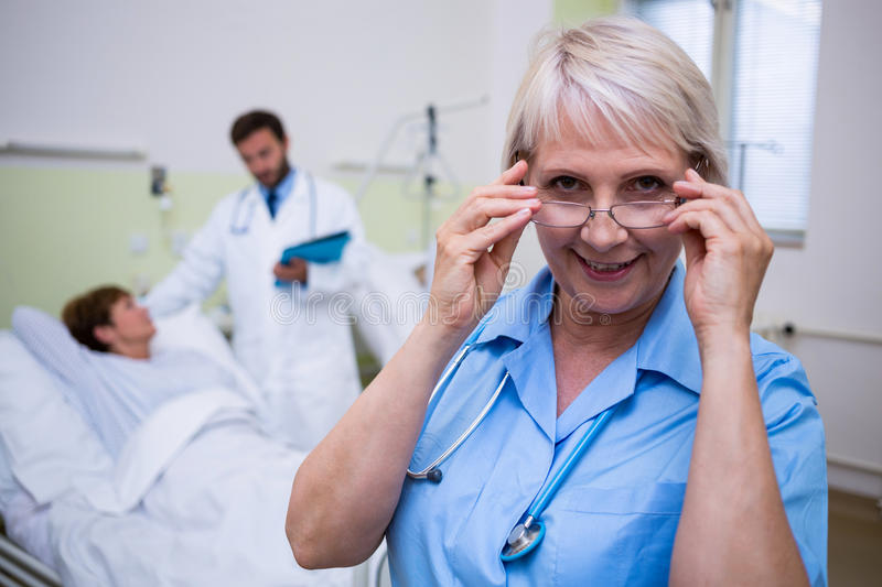 Portrait of smiling nurse wearing spectacle royalty free stock images