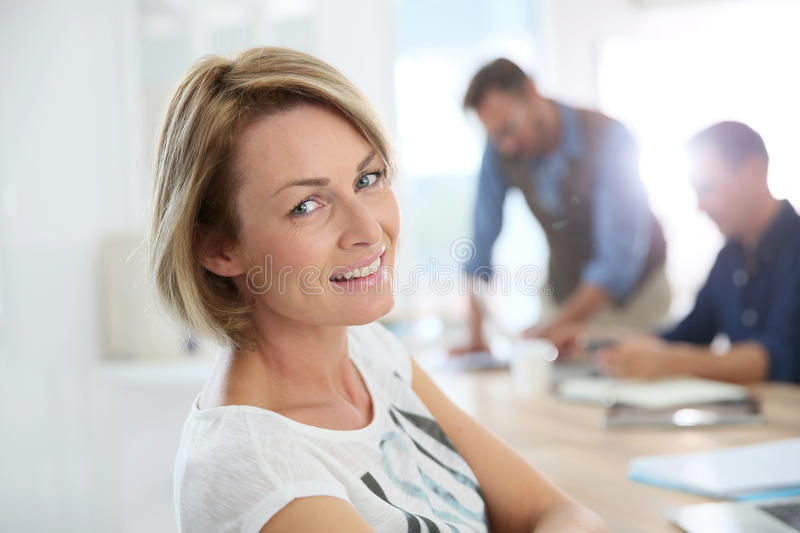 Portrait of smiling office worker amongst colleagues stock image
