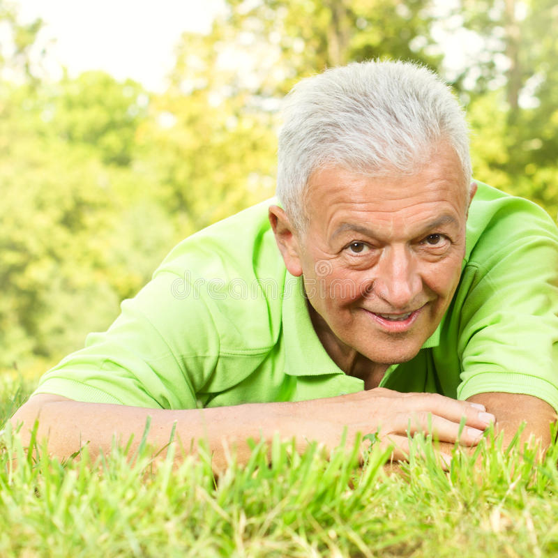 Portrait of smiling old man in the park stock photo