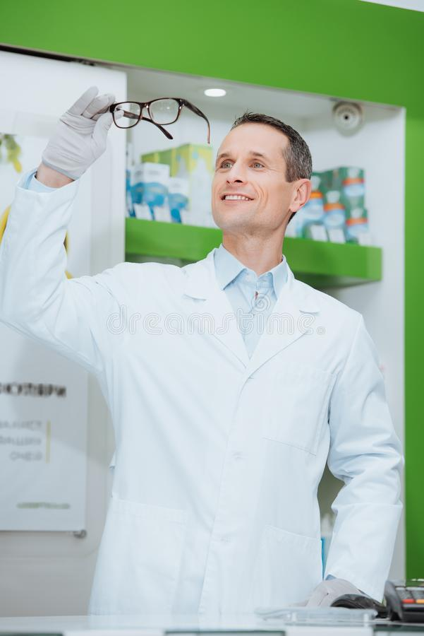 Portrait of smiling optometrist in white coat looking at eyeglasses in hands. In optics stock images
