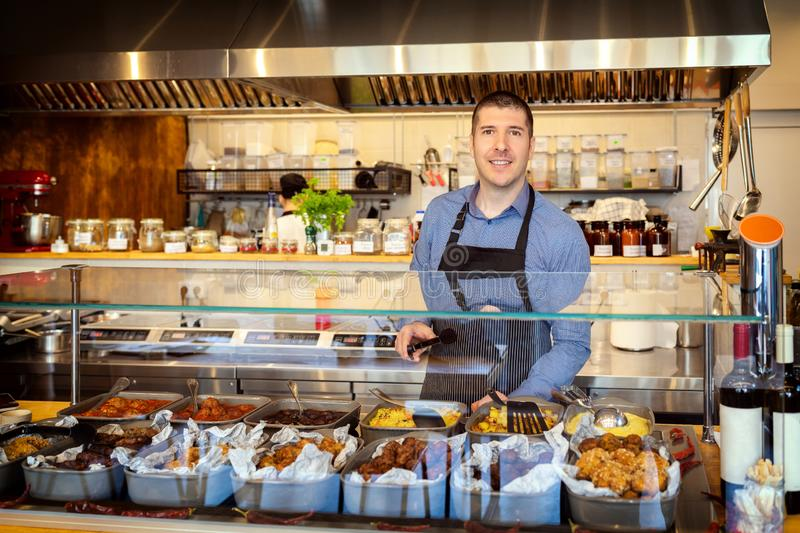 Portrait of smiling owner standing at his eatery serving food behind counter. – young entrepreneur wearing apron running small restaurant – happy royalty free stock photos