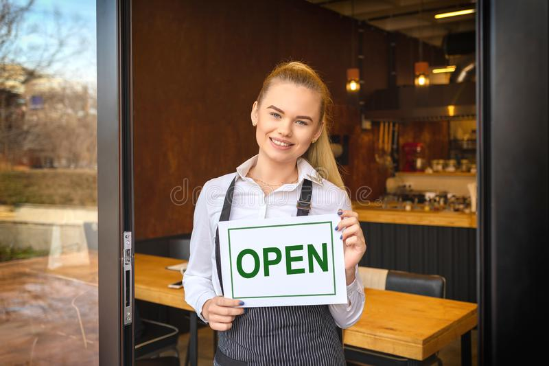 Portrait of smiling owner standing at restaurant door holding open sign, small family business stock photography
