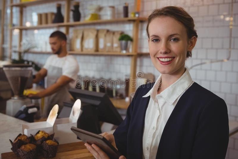 Portrait of smiling owner using tablet with waiter working in cafe royalty free stock image