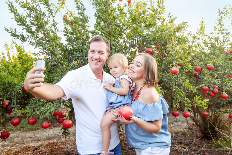 Portrait of smiling parents with baby girl daughter doing selfie photo with smart phone in the pomegrate fruit garden on the sunse stock photos