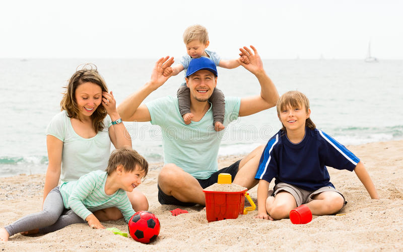 Portrait of smiling parents and their children on sand stock photo