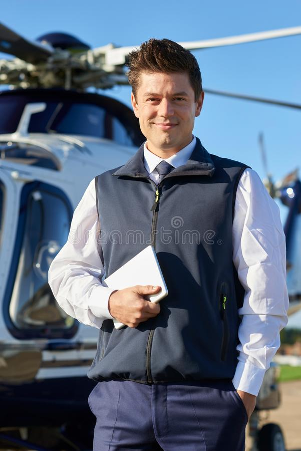 Portrait Of Smiling Pilot Standing In Front Of Helicopter With D royalty free stock image