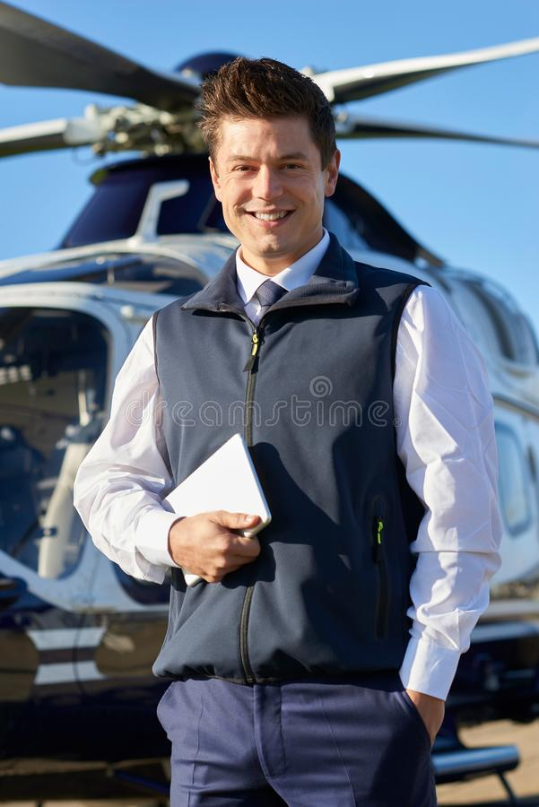 Portrait Of Smiling Pilot Standing In Front Of Helicopter With D stock photo