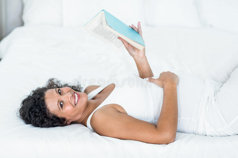 Portrait of smiling pregnant woman reading book royalty free stock photo