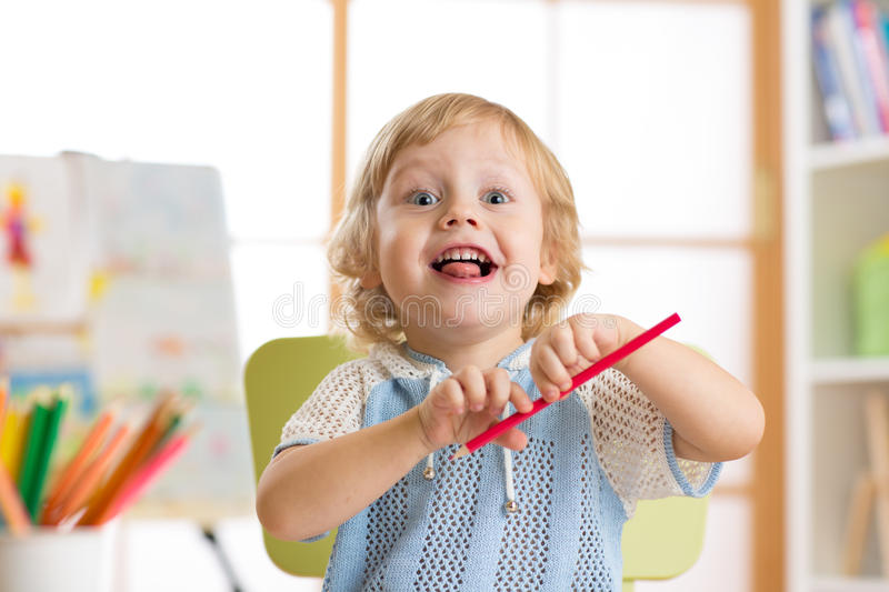 Portrait of a smiling preschool boy drawing stock photography