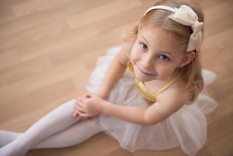 Portrait of smiling pretty diligent ballet girl sitting in white royalty free stock photos