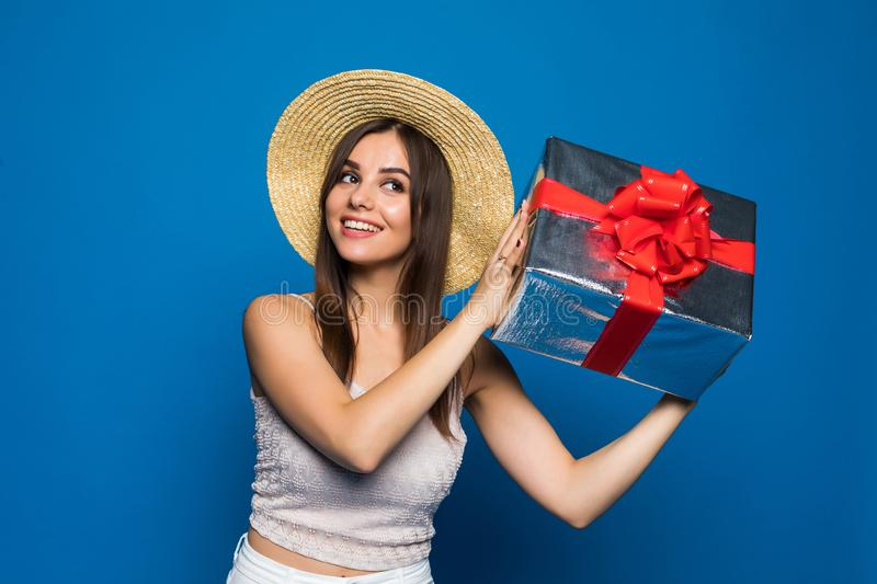 Portrait of a smiling pretty girl holding gift box isolated over blue background. Woman listen what inside of box. royalty free stock photography