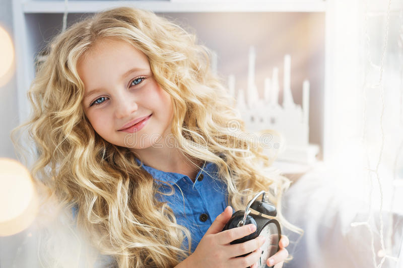 Portrait of smiling pretty little girl with a clock at hands near the window royalty free stock photos