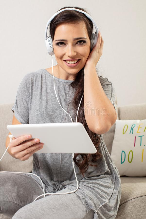 Portrait of a smiling pretty woman posing with headphones and tablet royalty free stock photo