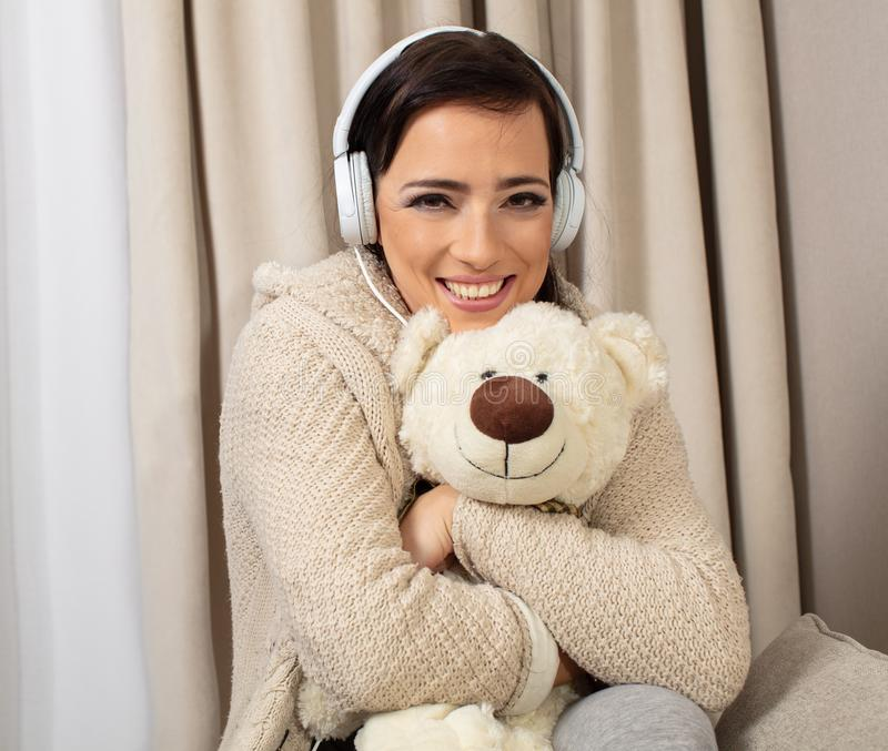 Portrait of a smiling pretty woman posing with headphones and teaddy bear stock image
