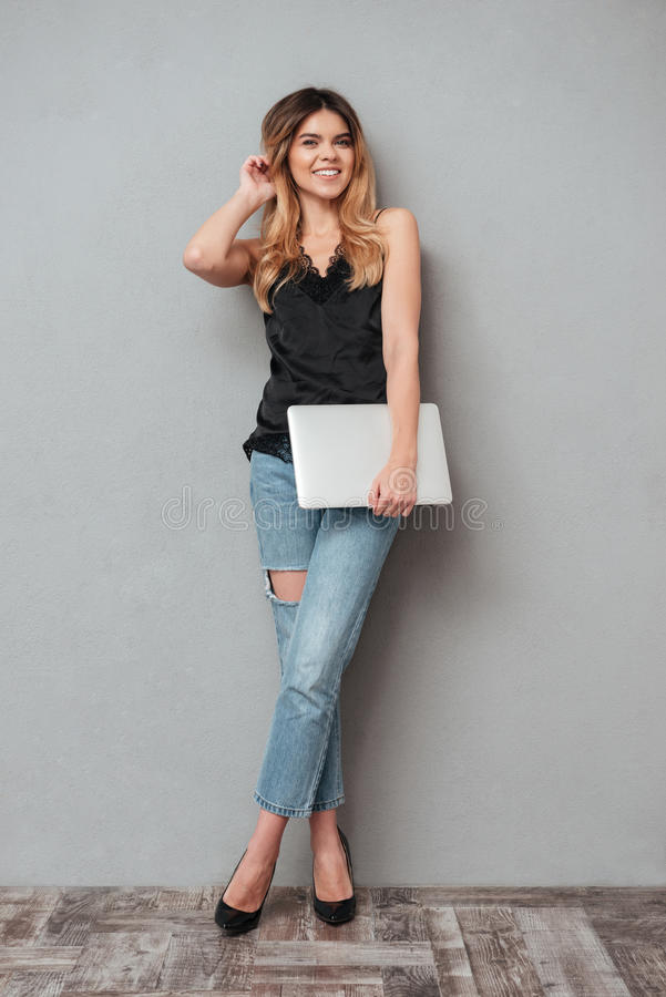 Portrait of a smiling pretty woman standing and holding laptop. Full length portrait of a smiling pretty woman standing and holding laptop isolated over grey royalty free stock photography