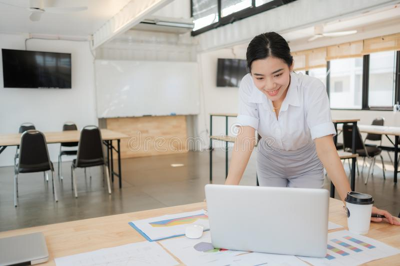 Portrait of smiling pretty young business woman on workplace, stock photography