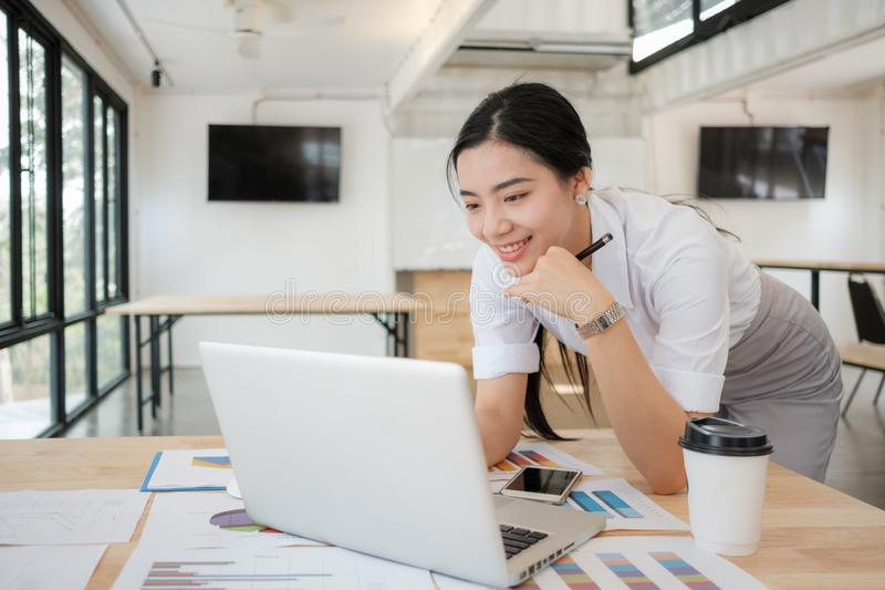 Portrait of smiling pretty young business woman on workplace, stock photo