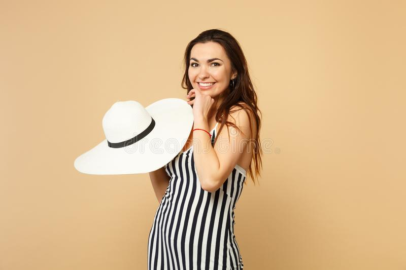 Portrait of smiling pretty young woman in black and white striped dress holding hat, looking camera  on pastel royalty free stock image