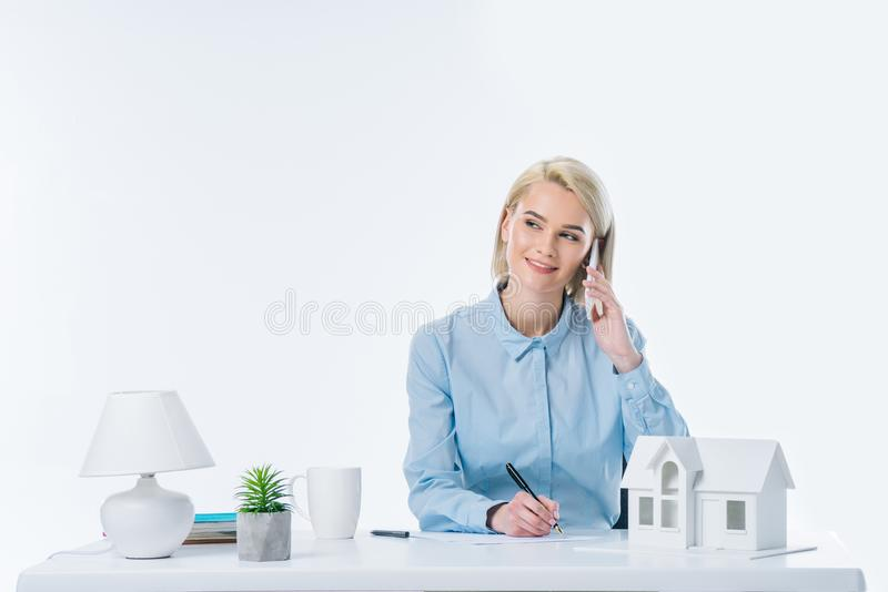 portrait of smiling real estate agent talking on smartphone at workplace stock images