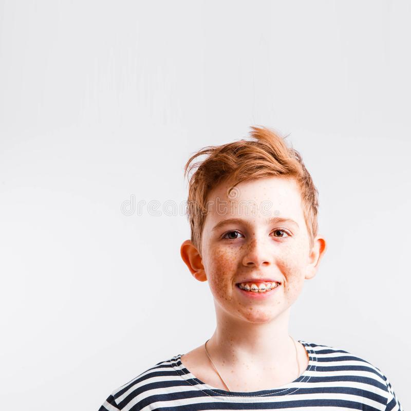 Portrait of a smiling red-haired boy with freckles and braces in a sailor suit on a white background, stock images