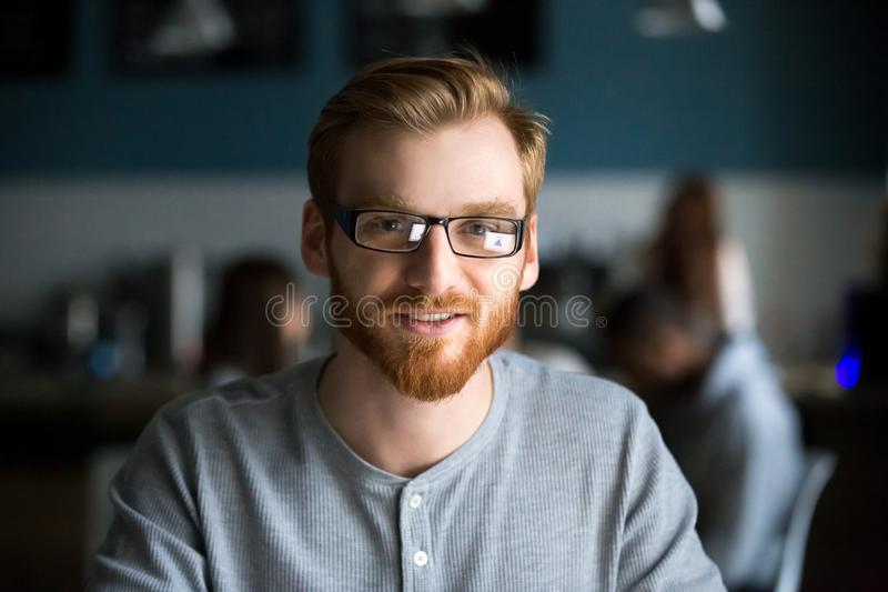 Portrait of millennial man posing sitting in cafe. Portrait of smiling red haired millennial men looking at camera sitting in cafe or coffeeshop, happy young stock photography