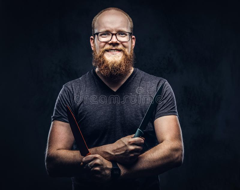 Portrait of a smiling redhead bearded male wearing glasses dressed in a gray t-shirt, standing with colored steel knives. In his hands. Isolated on a dark stock photos