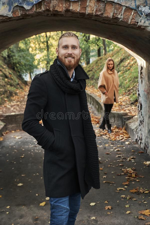 Portrait of smiling redhead guy under the old bridge arch. royalty free stock images