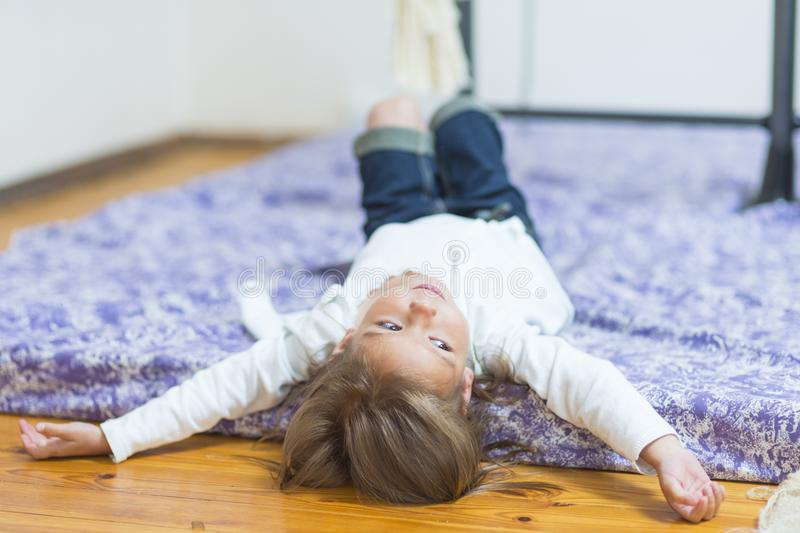 Portrait of Smiling Relaxing Caucasian Little Girl Posing on Floor. Wall Bars on Background. Horizontal Image Composition stock photography