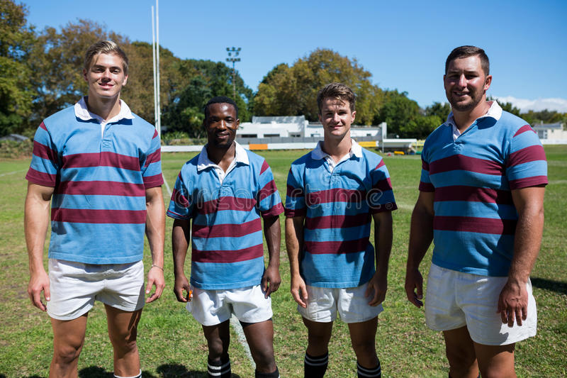 Portrait of smiling rugby team standing on grassy field stock photos
