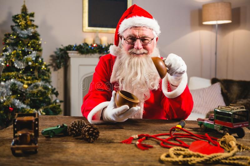 Smiling santa claus showing wooden bowl at home during christmas time royalty free stock photography