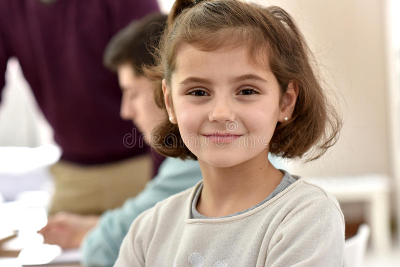 Portrait of smiling schoogirl at class stock photography