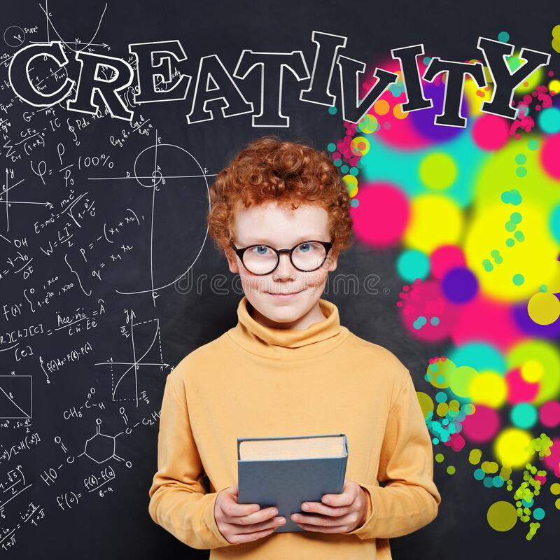 Portrait of a smiling schoolboy in a classroom against chalkboard with creativity inscription royalty free stock photo