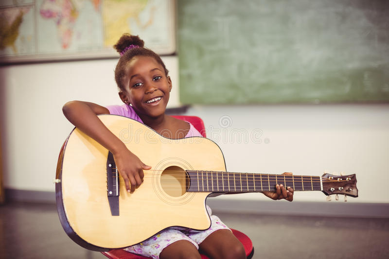 Portrait of smiling schoolgirl playing guitar in classroom stock photos