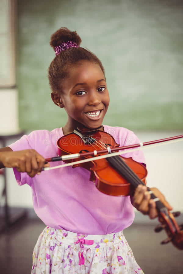 Portrait of smiling schoolgirl playing violin in classroom royalty free stock photos