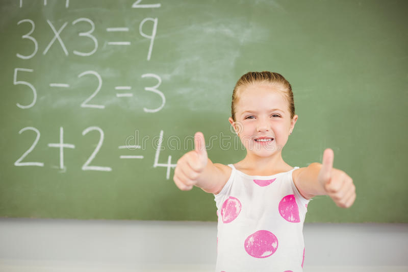 Portrait of smiling schoolgirl showing thumbs up in classroom stock photo