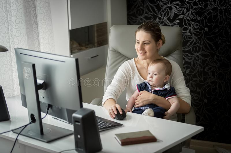 Portrait of smiling young selfemployed woman working at home office and looking after her baby son stock images