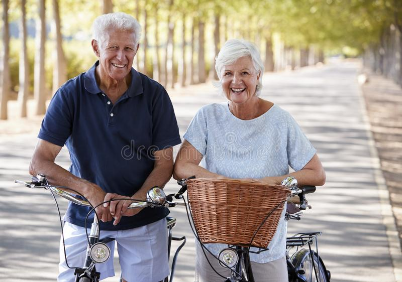 Portrait Of Smiling Senior Couple Cycling On Country Road stock photos