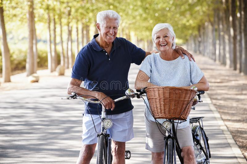 Portrait Of Smiling Senior Couple Cycling On Country Road royalty free stock photography