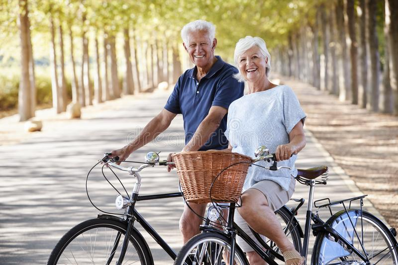 Portrait Of Smiling Senior Couple Cycling On Country Road stock image
