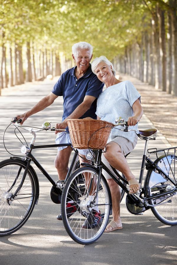 Portrait Of Smiling Senior Couple Cycling On Country Road royalty free stock photo