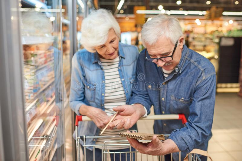 Seniour Couple Reading Shopping List. Portrait of smiling senior couple grocery shopping in supermarket, reading shopping list leaning on cart standing by royalty free stock photo