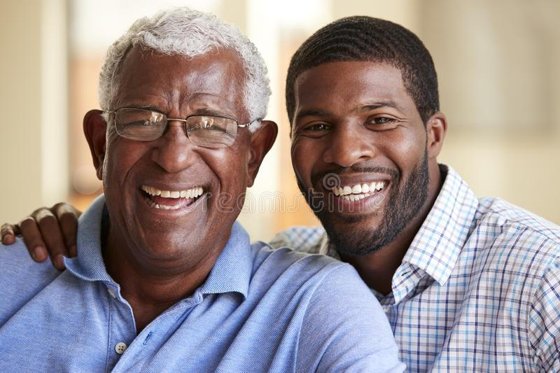 Portrait Of Smiling Senior Father Being Hugged By Adult Son At Home royalty free stock image