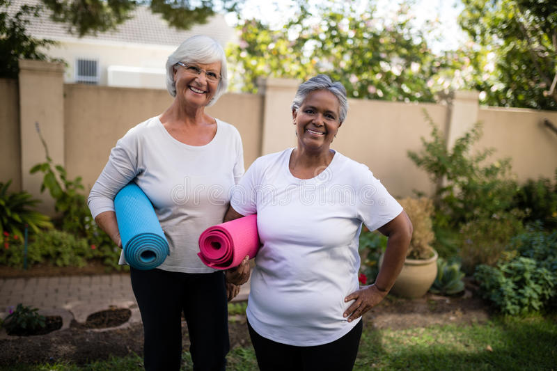 Portrait of smiling senior friends carrying exercise mats royalty free stock images