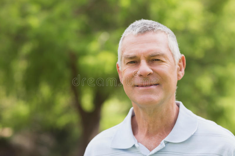 Portrait of a smiling senior man at park royalty free stock image